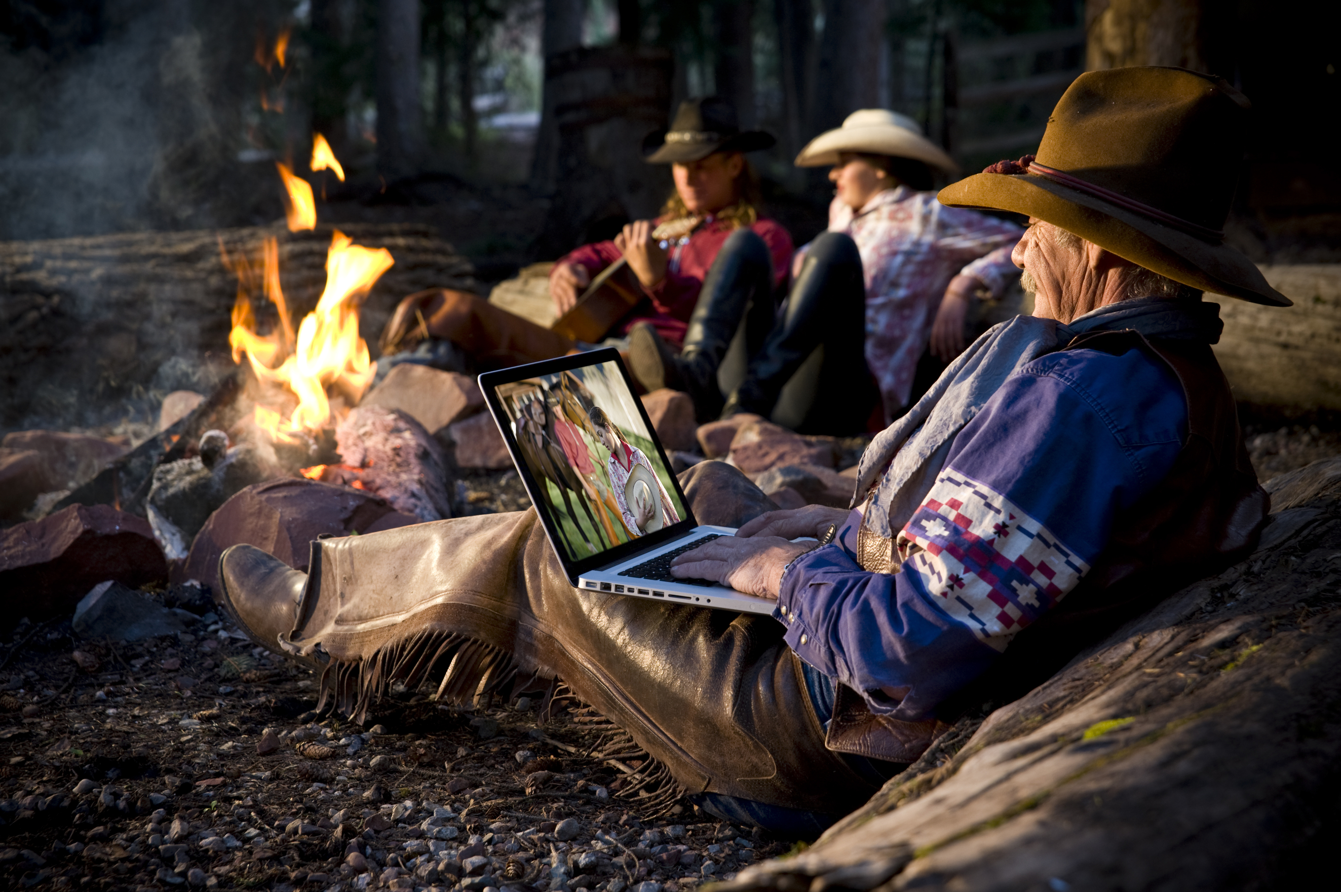 Old cowboy editing pictures on laptop around camp fire